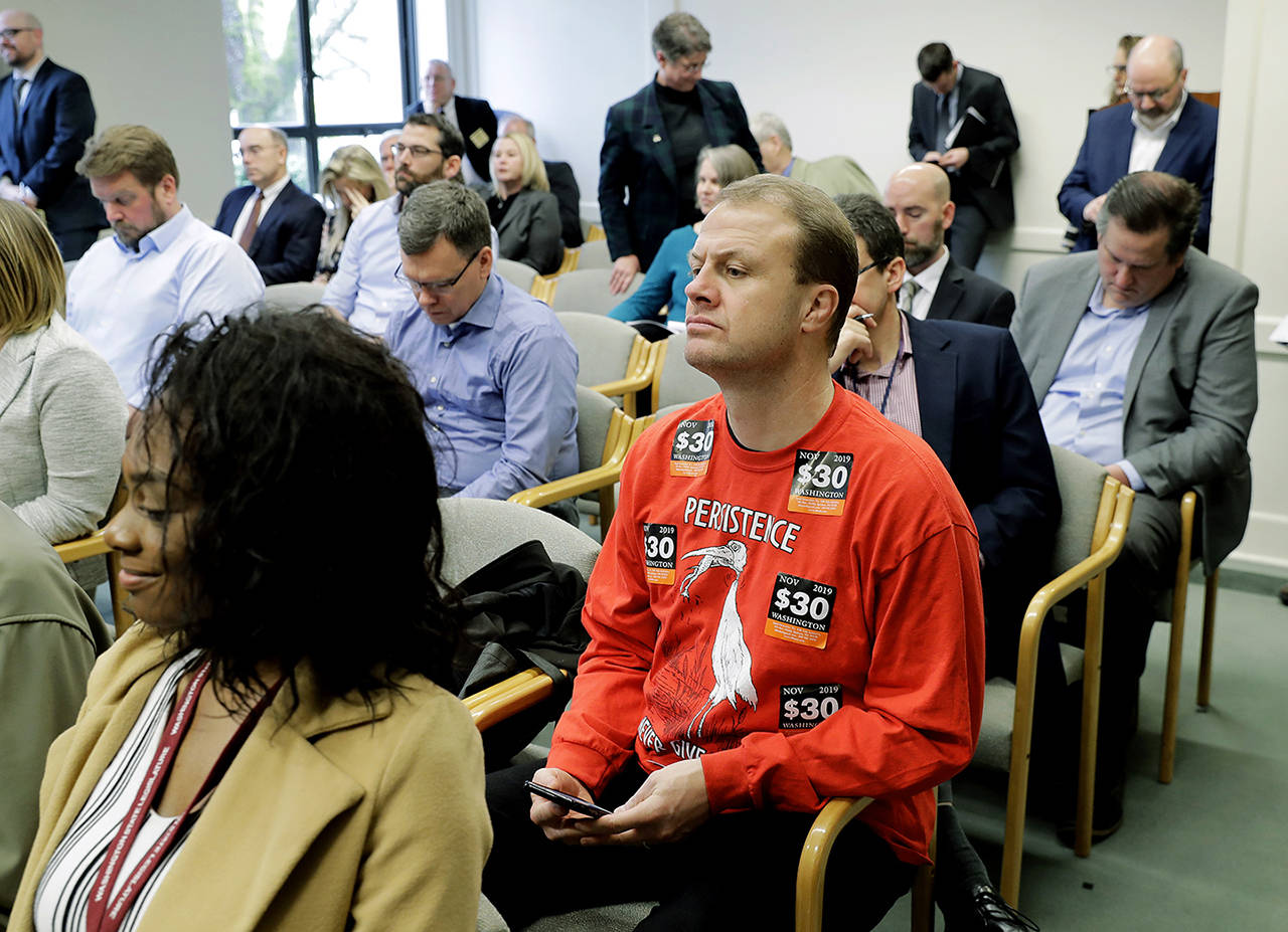 Anti-tax activist Tim Eyman wears a sweatshirt bearing stickers for his I-976 $30 car tabs initiative at the Associated Press Legislative Preview at the Capitol in Olympia on Jan. 10. (AP Photo/Ted S. Warren)