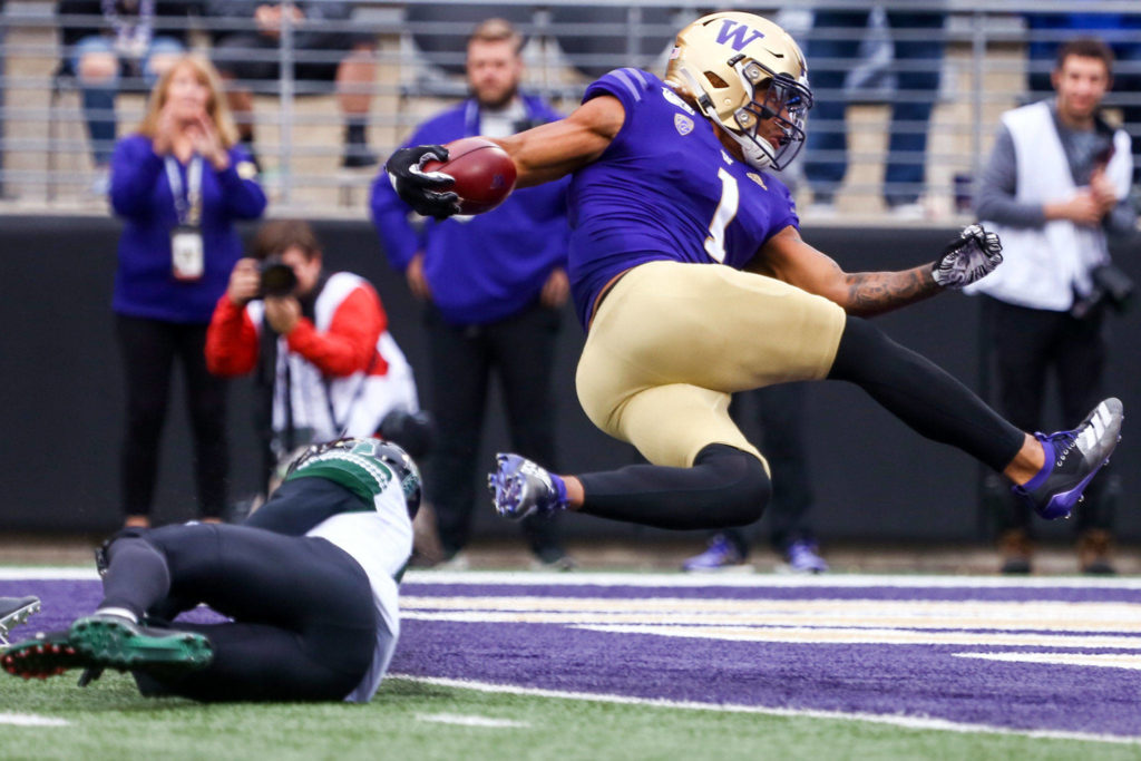 Washington's Hunter Bryant bounces into the end zone and a touchdown off Hawai'i's Cortez Davis Saturday evening at Husky Stadium in Seattle on September 14, 2019. Husky won 52-20. (Kevin Clark / The Herald)