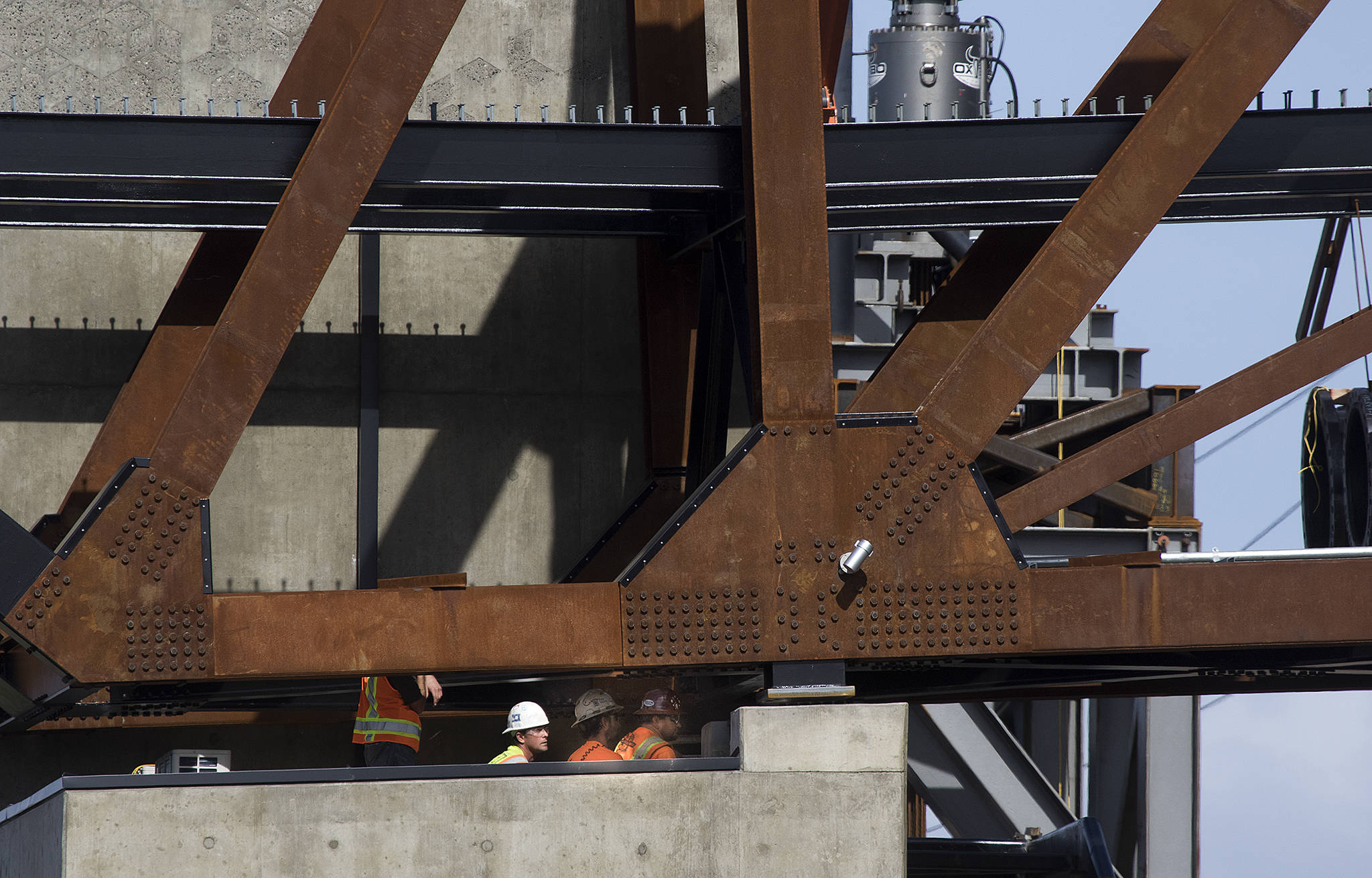 Workers watch from below as the $20 million Grand Avenue Park Bridge was slowly lowered into place above Marine View Drive on Wednesday in Everett. (Andy Bronson / The Herald)