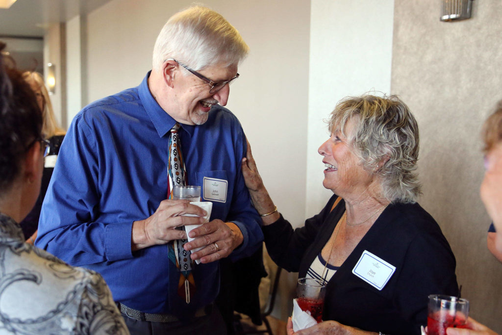 John Galbreath (left) and Joye Church share a laugh during the 10th Annual Snohomish County Sports Hall of Fame Banquet Wednesday evening at Angel of the Winds Arena in Everett. (Kevin Clark / The Herald)