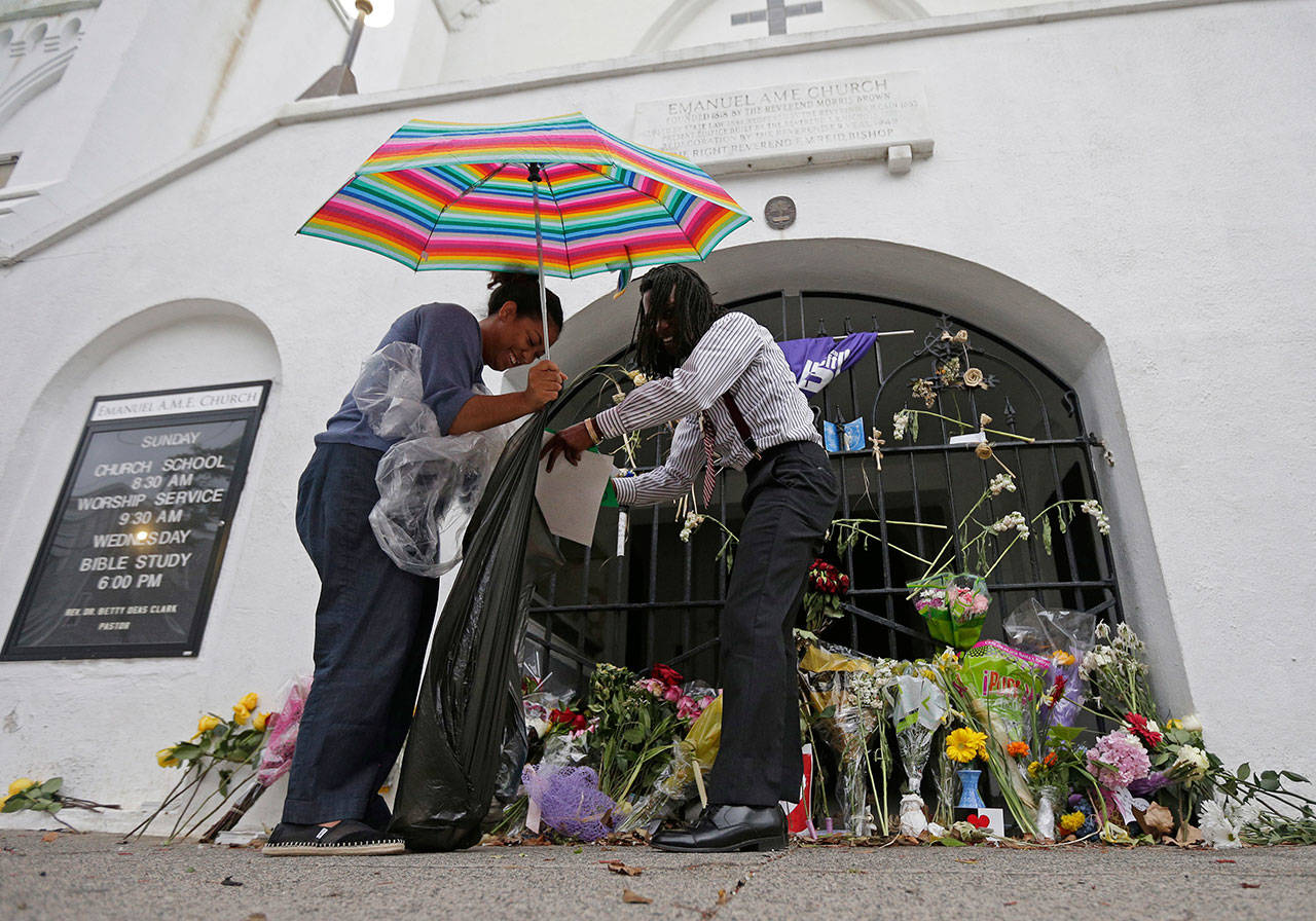 Barrye Browne (left) and Daron Calhoun collect memorials placed at Mother Emanuel AME Church in Charleston, S.C., on July 17, 2016, the first anniversary of the killing of nine black parishioners during bible study. The gunman who killed the worshippers had been arrested on drug charges just weeks prior to the shooting. Although that arrest should have prevented him from purchasing the pistol he used in the attack, the examiner reviewing the sale never saw the arrest report because the wrong agency was listed in state criminal history records. (Chuck Burton / Associated Press file photo)