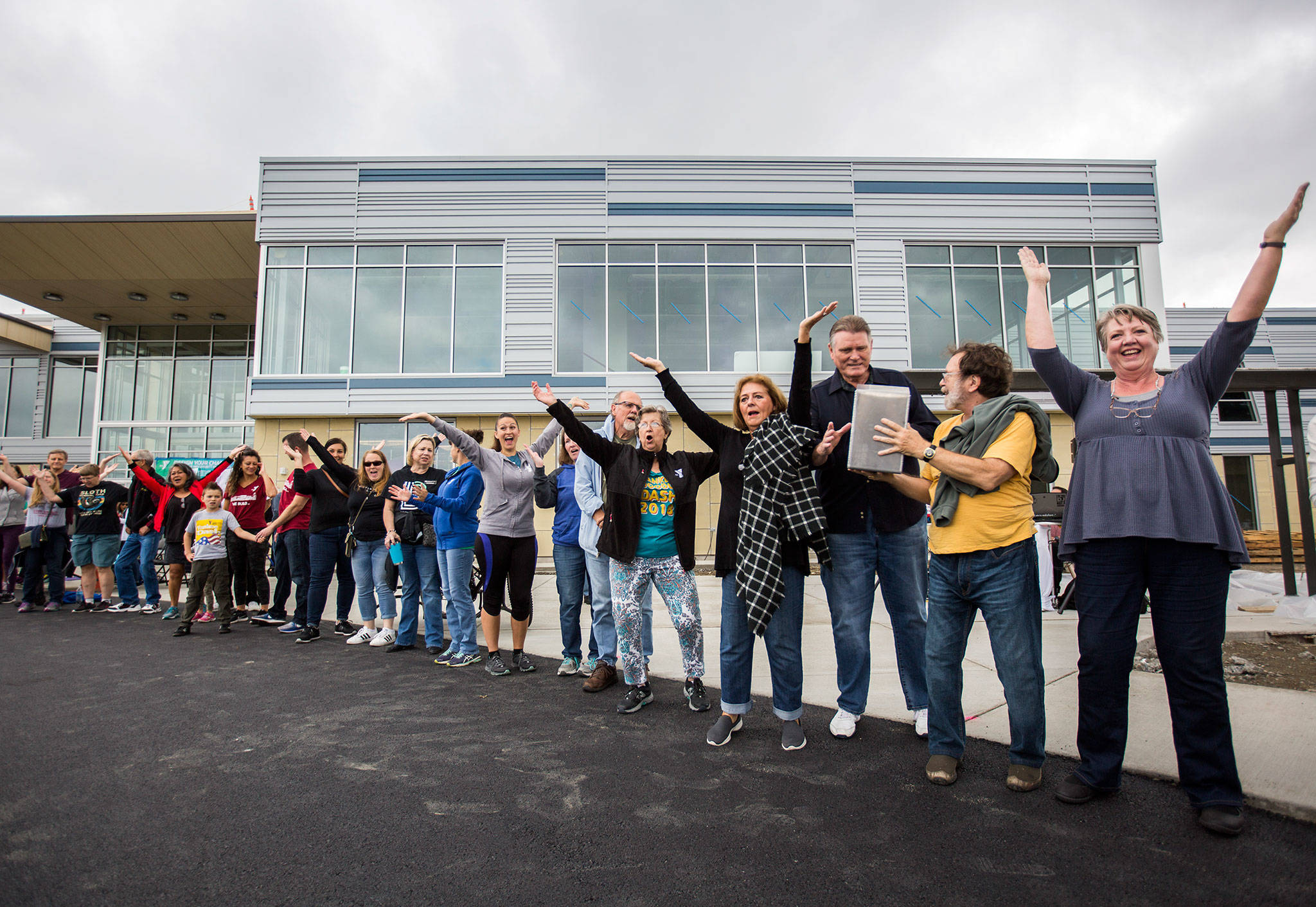 "People gather in front of the new YMCA location to pass the new time capsule into the building while dancing to ""YMCA"" during the YMCA's time capsule ceremony on Saturday, Sept. 21, 2019 in Everett, Wash. (Olivia Vanni / The Herald)"