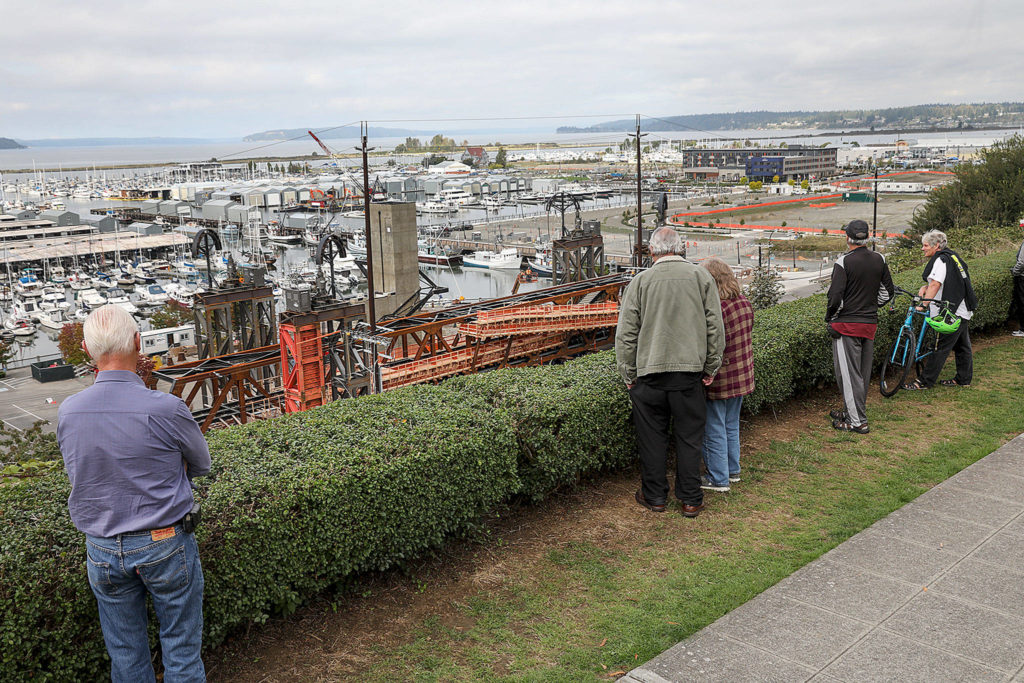 A small crowd gathered at Grand Avenue Park to watch crews install the steel bridge. (Lizz Giordano / The Herald)