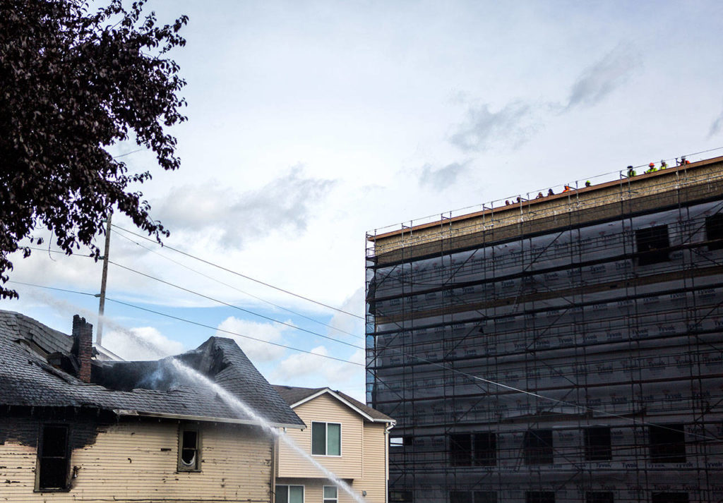 Construction workers watch from the top of a building while water is sprayed on a house that caught fire. (Olivia Vanni / The Herald)