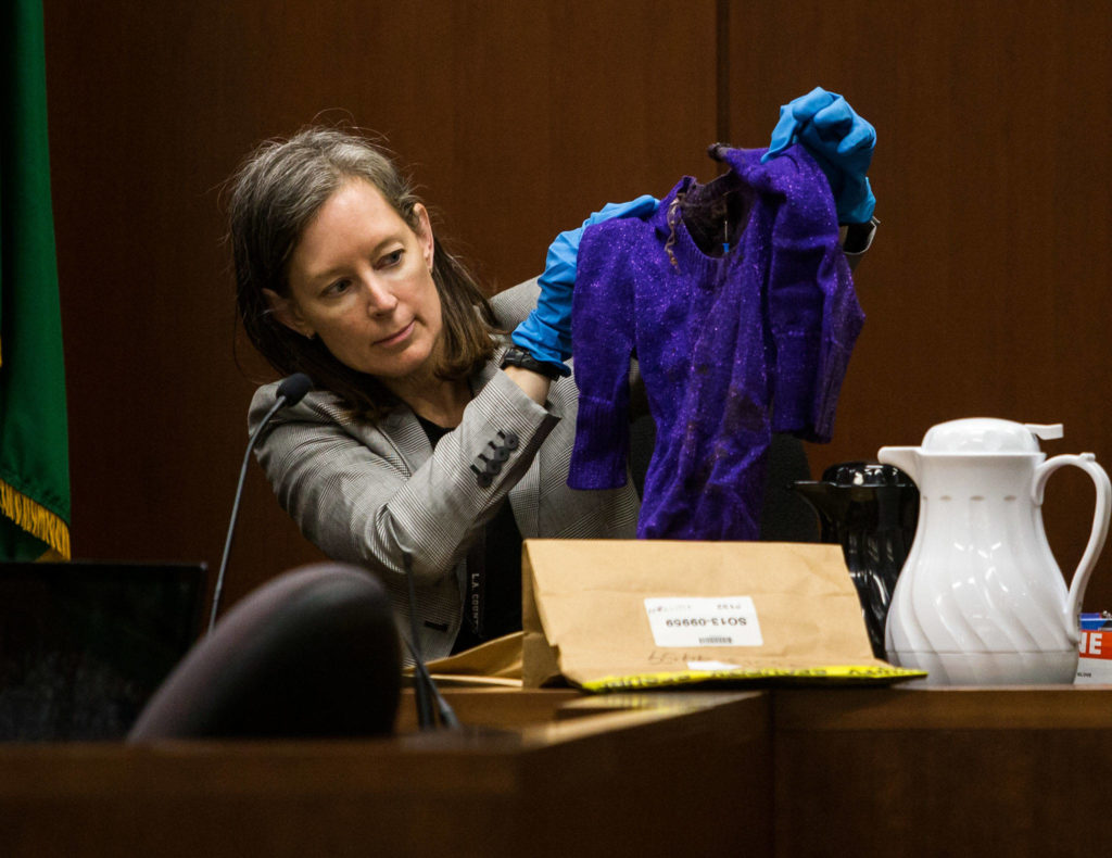 Jane Jorgensen, an investigator for the Snohomish County Medical Examiner's Office, holds up a sweater found on Phillipa Evans-Lopez's body. The investigator testified at the trial of Anthony Garver at the Snohomish County Courthouse on Friday, Oct. 4, 2019 in Everett, Wash. (Olivia Vanni / The Herald)