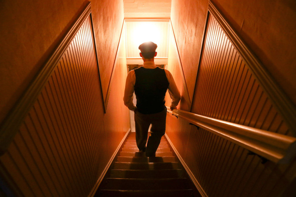 Edmundo Olanu descends the stairs at the Grimm House. (Kevin Clark / The Herald)