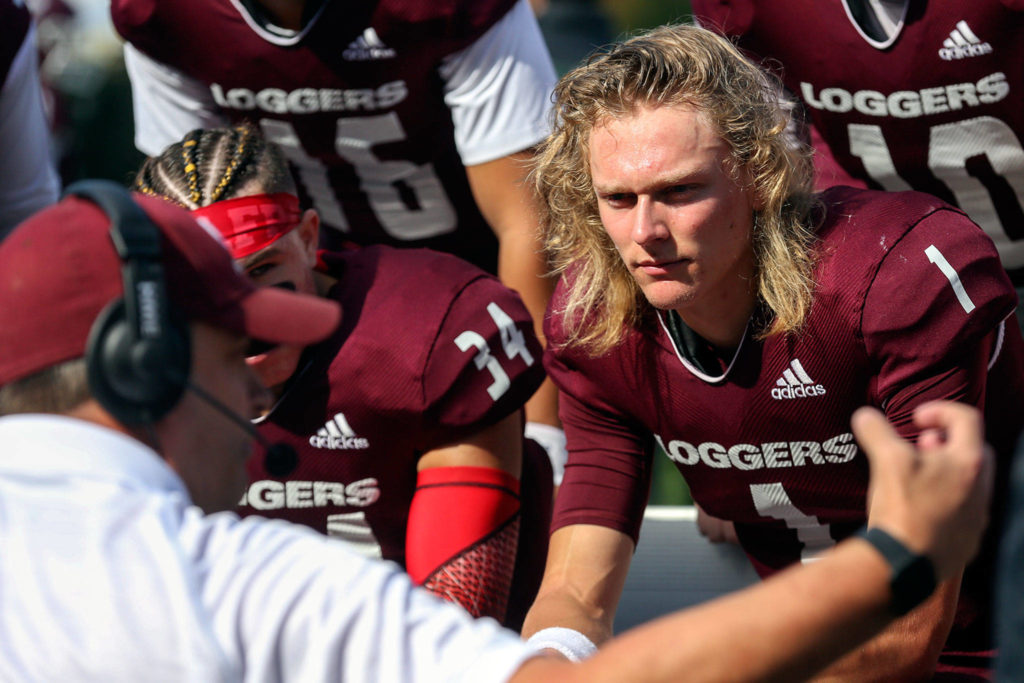 Murdock Rutledge (right), an Everett High School alumnus, is in his second season at quarterback for the University of Puget Sound. (Kevin Clark / The Herald)