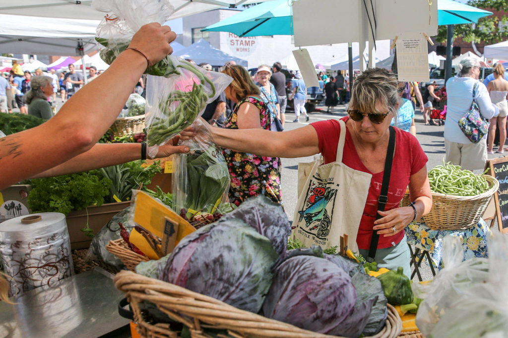 Nancy Cody shops at a produce stand this summer at the Everett Farmers Market. (Kevin Clark / Herald file)