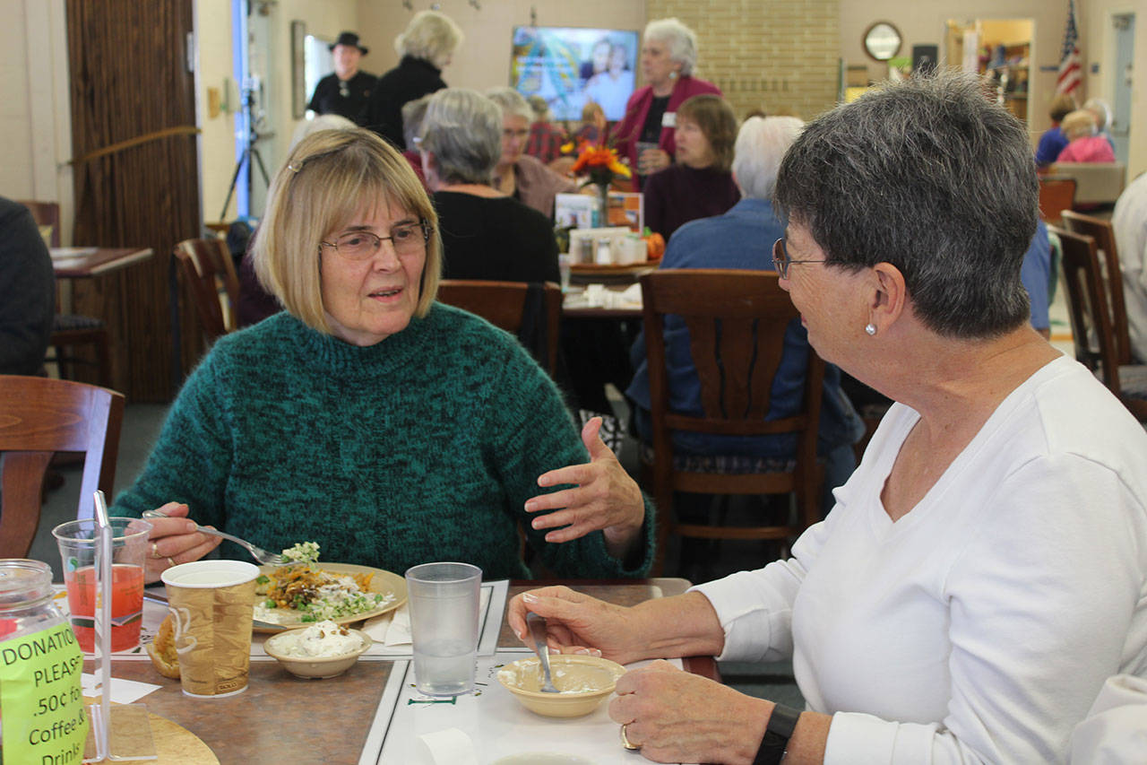 Volunteer Bobbie Olzta, left, and Island Senior Resources board member Julie Joselyn share a meal at the opening of Leo's Place, a new intergenerational dining hall on Whidbey Island. (Wendy Leigh / South Whidbey Record)