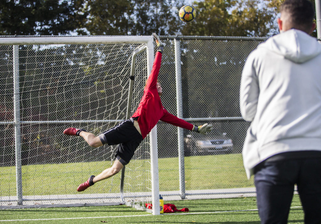 Everett Community College men's soccer goalkeeper Cameron Beardsley dives to make a save during the Trojans' Oct. 8 practice at Kasch Park in Everett. (Olivia Vanni / The Herald)