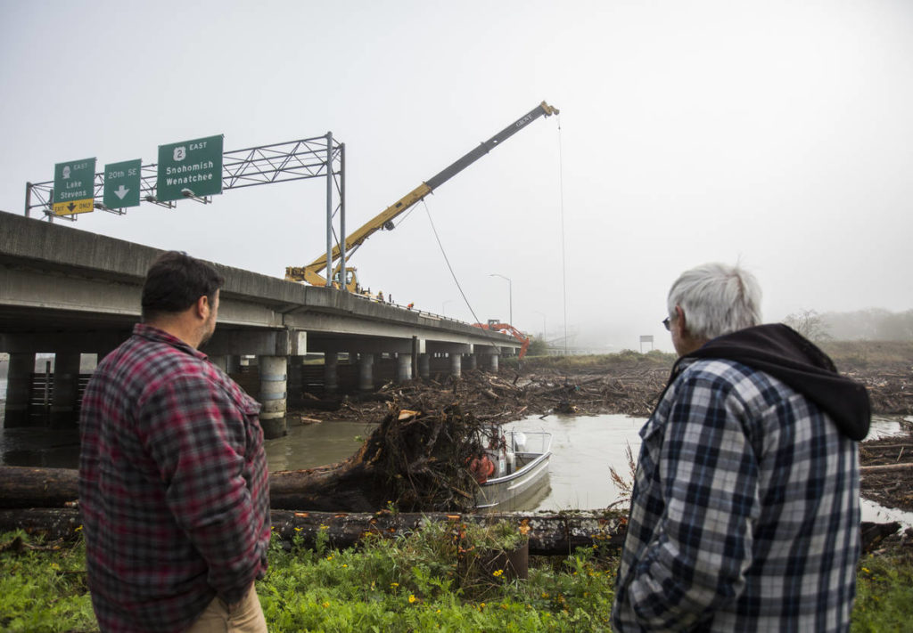 Local residents watch as an excavator, crane and boat work to try to move out logs jammed against the pilings along the eastbound lanes of State Route 2 in Ebey Slough on Wednesday in Everett. (Olivia Vanni / The Herald)