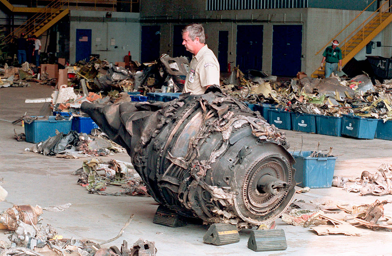 A mechanic walks past the remains of an engine from USAir Flight 427 in a hangar in 1994 in Coraopolis, Pennsylvania. (AP Photo/Gene J. Puskar)