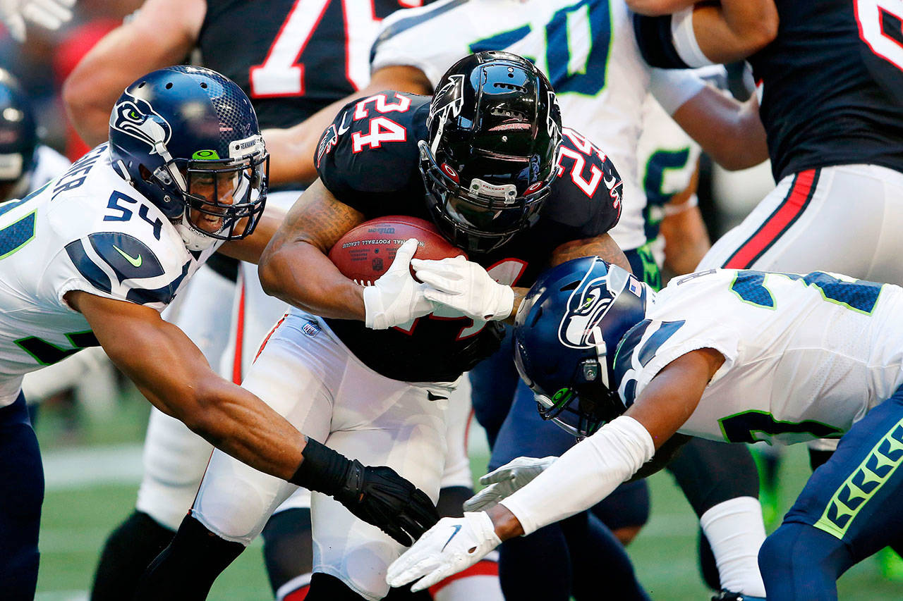Seattle's Bobby Wagner (left) reaches out to tackle Atlanta's Devonta Freeman (24) during the Seahawks' win over the Falcons on Sunday in Atlanta. (AP Photo/John Bazemore)