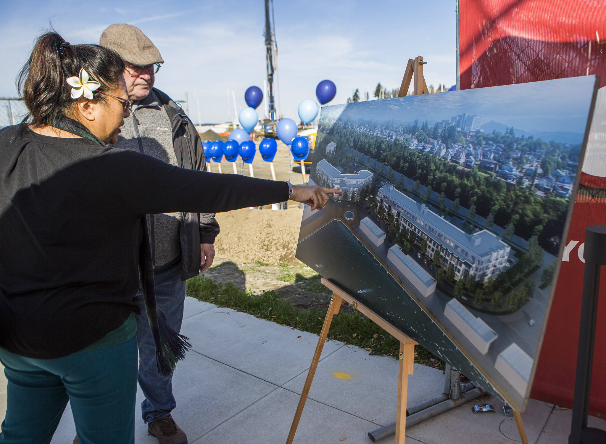 Future residents try to locate where their apartment may be on a pasteboard of the apartment buildings at the groundbreaking for the Waterfront Place Apartments along the Everett waterfront Wednesday . (Olivia Vanni / The Herald)