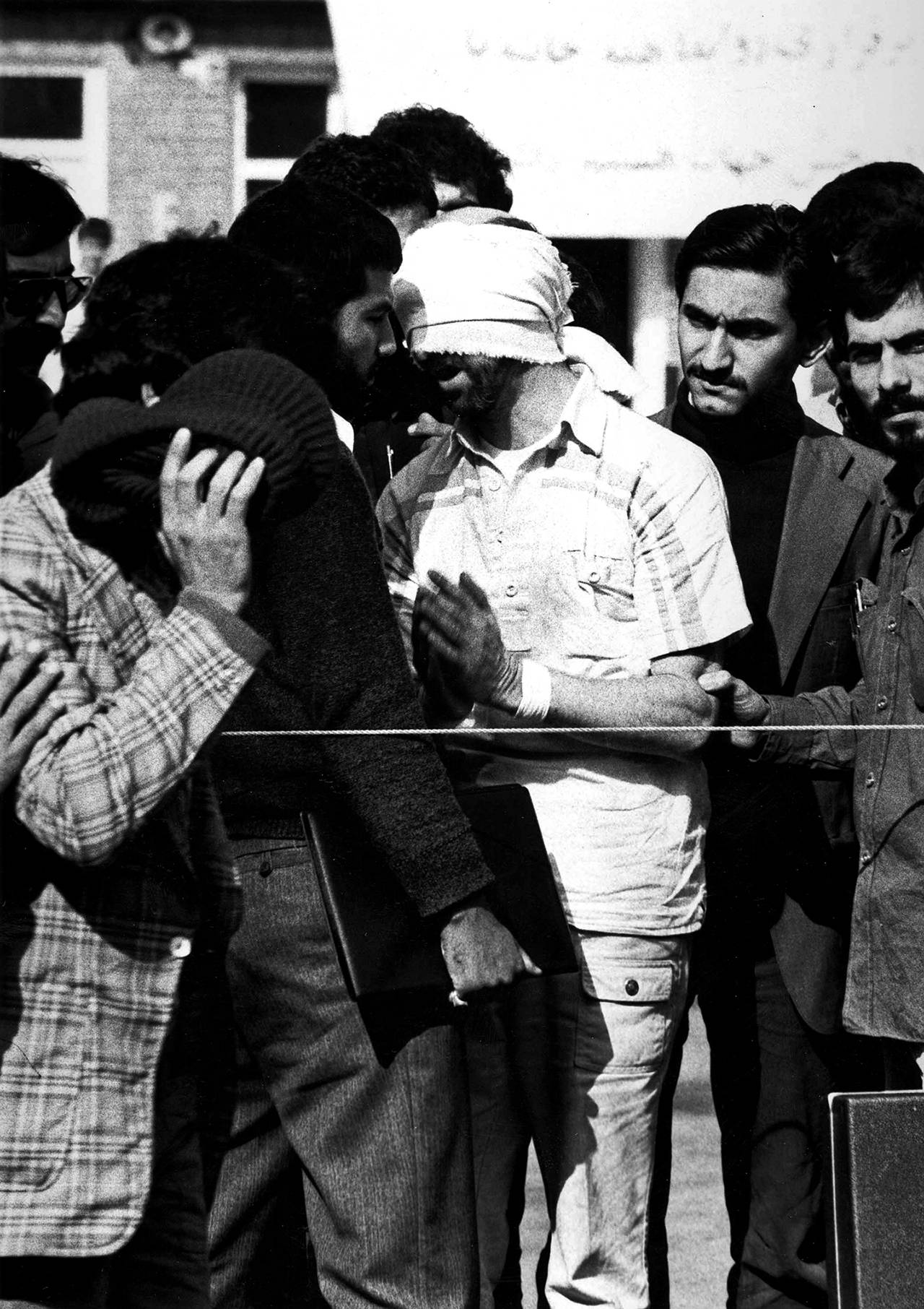 In this undated image, one of U.S. hostages, blindfolded and with his hands bound, is being displayed to the crowd outside the U.S. Embassy in Tehran by Iranian hostage takers. (AP Photo)