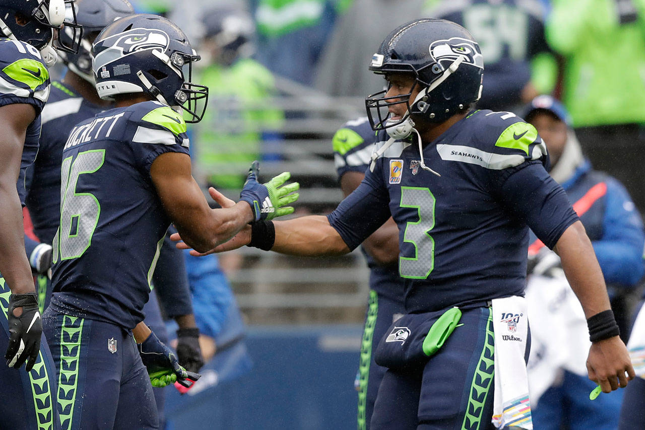 Seahawks quarterback Russell Wilson (3) greets wide receiver Tyler Lockett (16) after Lockett caught a pass from Wilson for a touchdown during the first half of a game against the Ravens on Oct. 20, 2019, in Seattle. (AP Photo/John Froschauer)