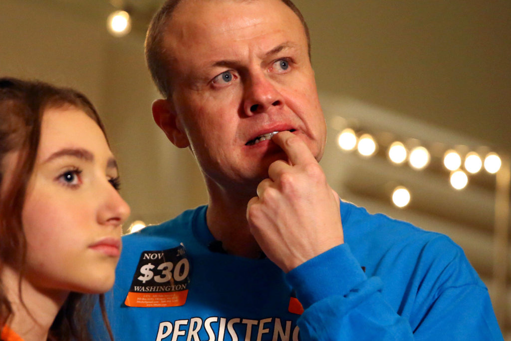 Tim Eyman (right) with his daughter Riley Eyman react to the early numbers Tuesday evening at Hyatt Regency in Bellevue. (Kevin Clark / The Herald)