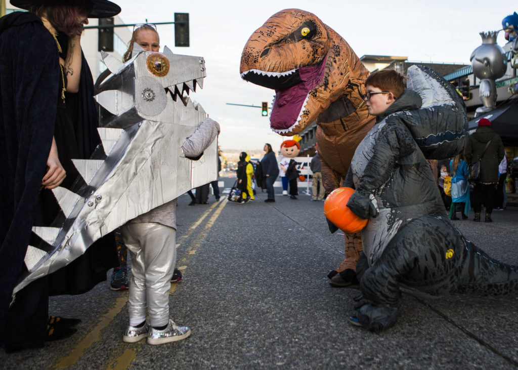 A group of people in dinosaur costumes greet each other during Downtown Trick-or-Treating on Oct. 31, 2019 in Everett, Wash. (Olivia Vanni / The Herald)