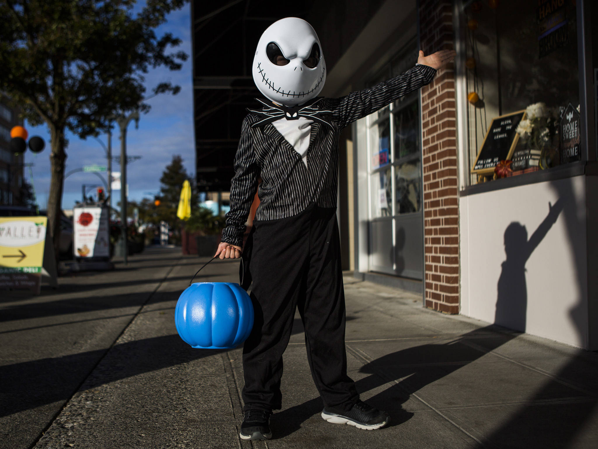 Samuel Pincus, dressed as Jack Skellington from Nightmare Before Christmas, gestures to people to come and grab candy during downtown trick-or-treating Thursday in Everett. (Olivia Vanni / The Herald)
