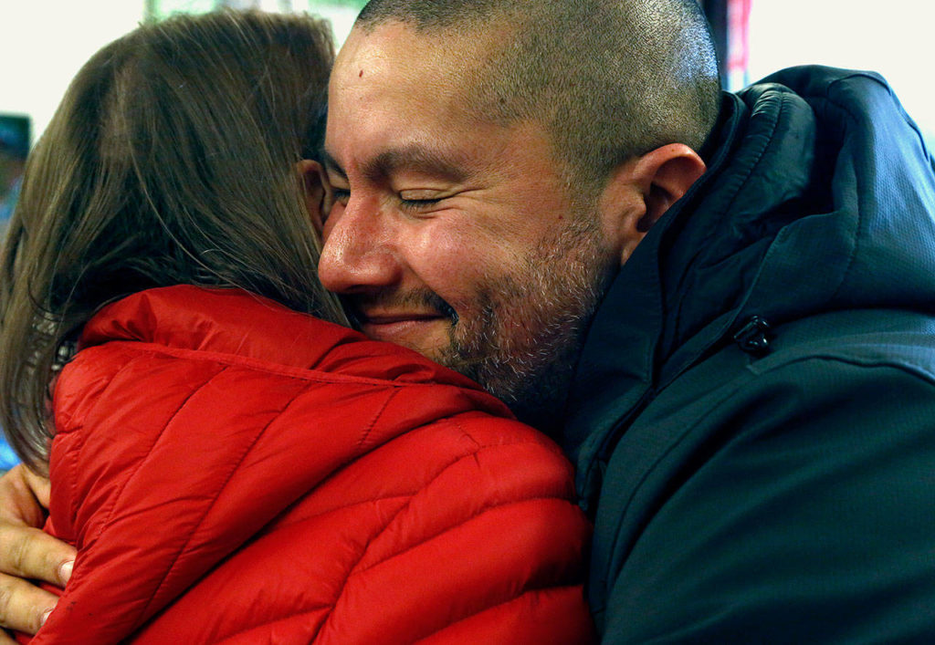 Fernando Moratalla, a U.S. Marine veteran, hugs Myra Rintamaki at the Veterans Resource Center at Edmonds Community College Tuesday. Rintamaki is a Gold Star Mother whose Marine Corps son Steven was killed in Iraq in 2004. Moratalla is an immigrant from Venezuela. (Dan Bates / The Herald)