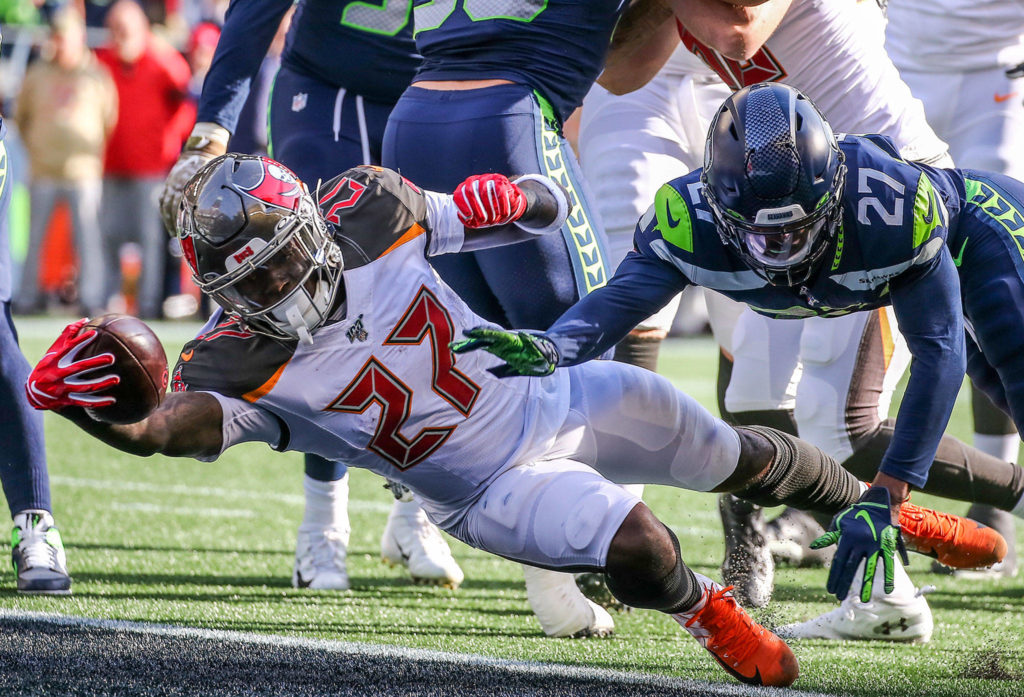Buccaneers Ronald Jones II stretches a touchdown against the Seahawks Marquise Blair Sunday afternoon at CenturyLink Field in Seattle on November 3, 2019. (Kevin Clark / The Herald)