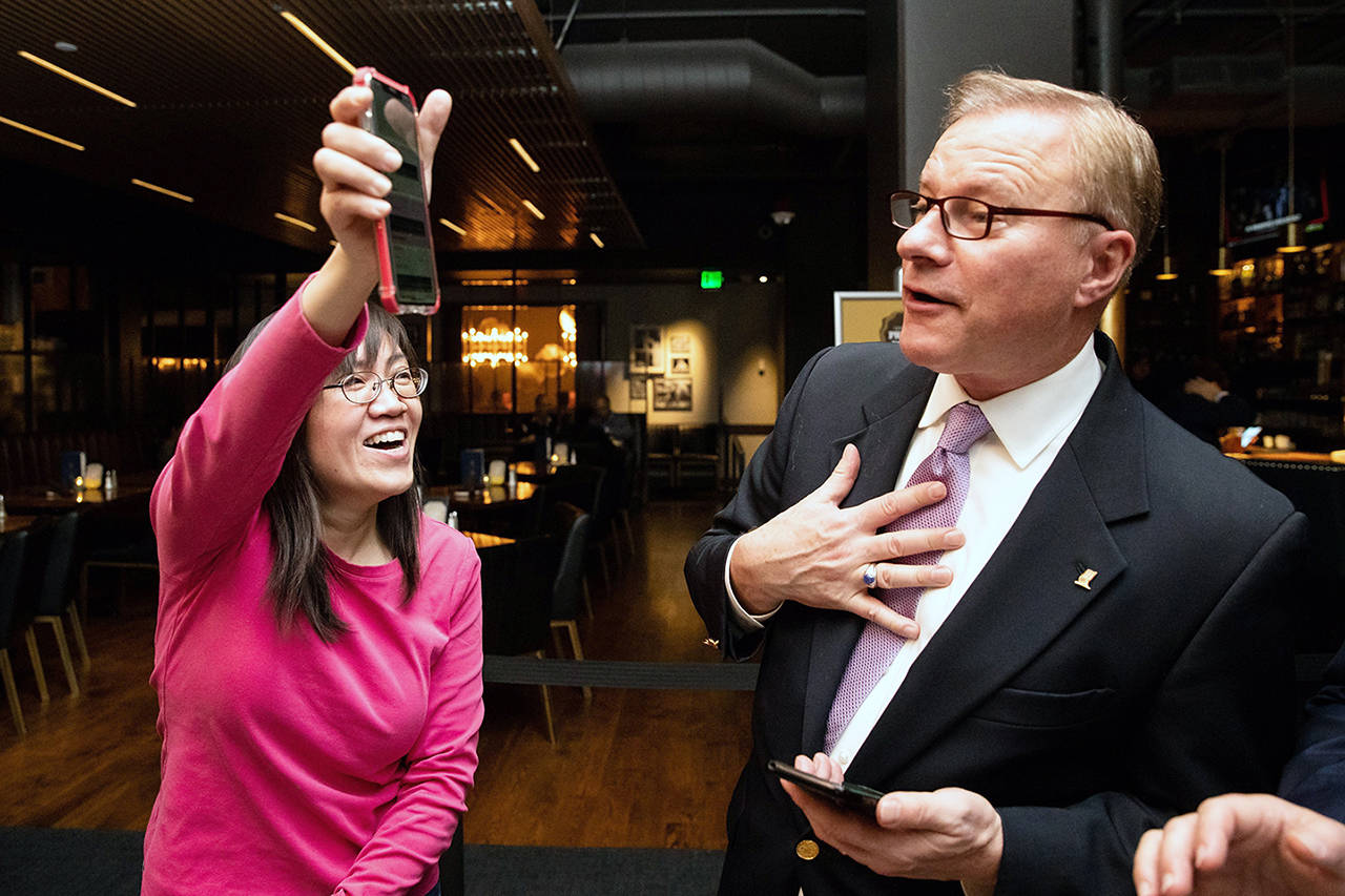 Campaign leader Linda Yates celebrates an early lead in the polls alongside KVI morning talk show host John Carlson during the anti-affirmative action group Reject Referendum 88 campaign's election-watching event at 13 Coins in Bellevue on Tuesday. (Andy Bao/The Seattle Times via AP)