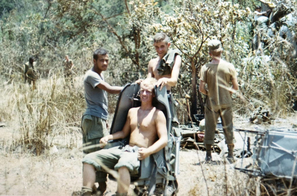 Greg Doering sits in a seat as he and his squad pull security duty while recovering parts from a downed helicopter in Vietnam. (Photo courtesy of Greg Doering)