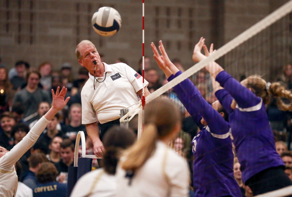Referee Pat Kaminske tracks play at Arlington High School against Oak Harbor on October 24, 2019. Arlington won in straight sets. (Kevin Clark / The Herald)