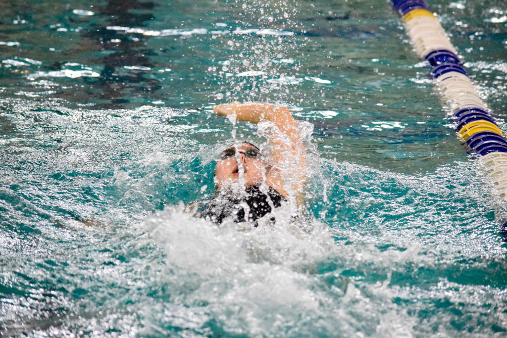 Jackson's Mia Chang swims in the girls 100 yard backstroke of the 4A Girls Northwest District Championship on Nov. 9 at the Snohomish Aquatic Center. Chang won with a time of 54.56, which is a meet record. (Katie Webber / The Herald)