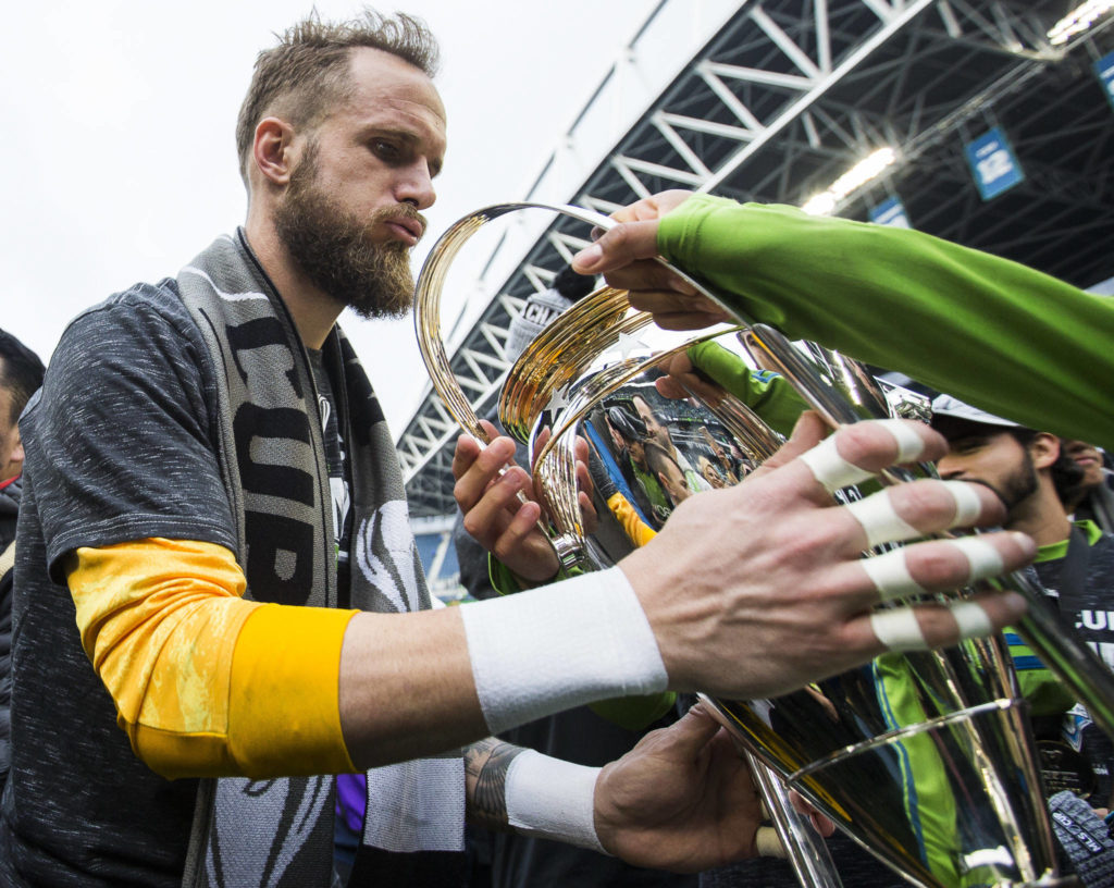 Sounders goalkeeper Stefan Frei grabs the MLS Cup after the game on Nov. 10, 2019 in Seattle, Wash. (Olivia Vanni / The Herald)