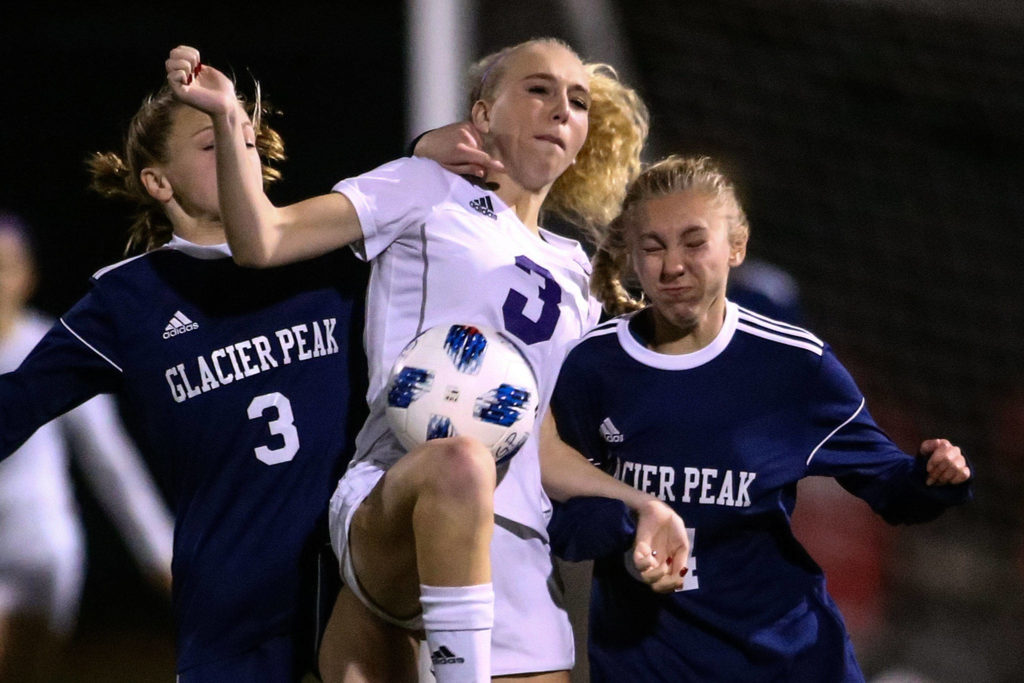 Glacier Peak's Chloe Seelhoff (right) and Annika Lambott (right) fight with Sumner's Madison Morgan for control Wednesday evening at Glacier Peak High School in Snohomish on November 13, 2019. Sumner won 2-1. (Kevin Clark / The Herald)