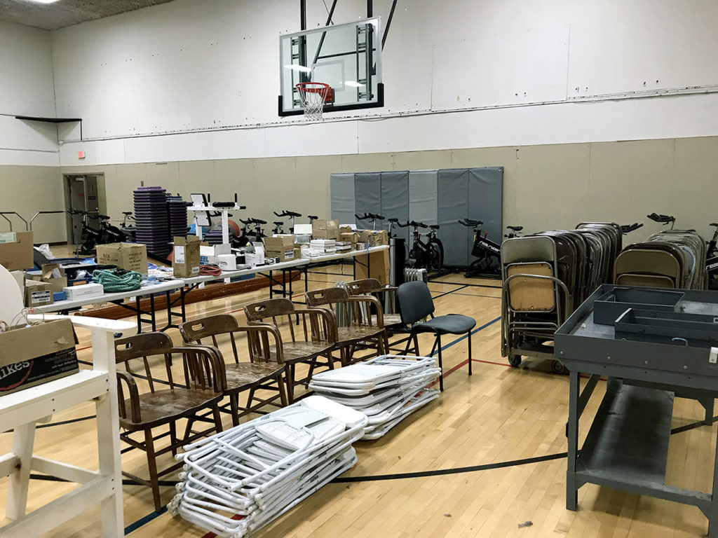 Extra equipment, including chairs and exercise bikes, is stored in a gym at the former Everett YMCA. It's all going to be up for sale at a garage sale next month. (Stephanie Davey / The Herald)