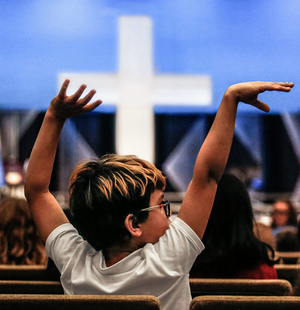 Braylon McMillen, a fifth-grader at Northshore Christian Academy, moves to the music of the jazz band Wednesday during a celebration of his school being recognized as a National Blue Ribbon School for 2019. The event included music, speeches and prayer. (Dan Bates / The Herald)