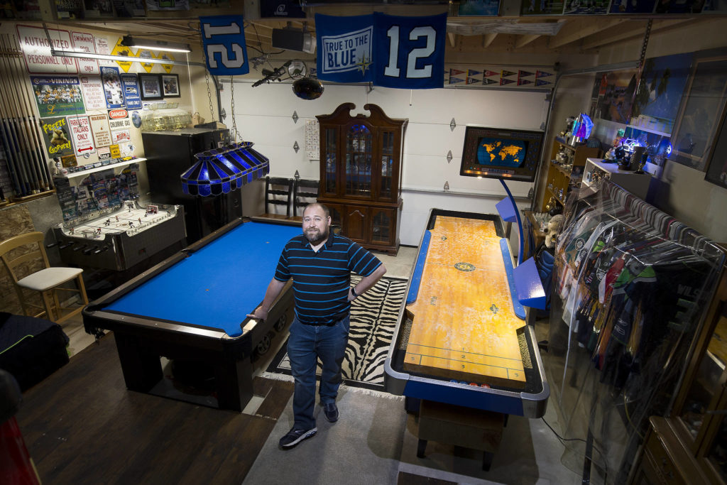 Josh Whall in his gaming room, the garage, at his home on Nov. 22 in Marysville. The room has shuffleboard, hockey table and a pool table, and even a collection of the patches from each of the MLB's All-Star games. (Andy Bronson / The Herald)