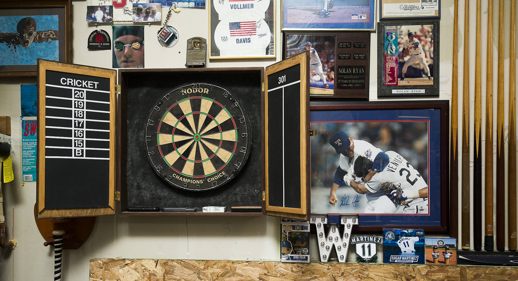 Pictures of Baseball Hall of Fame pitcher Nolan Ryan and swimming memorabilia surround a dartboard made by Josh Whall's father. (Andy Bronson / The Herald)