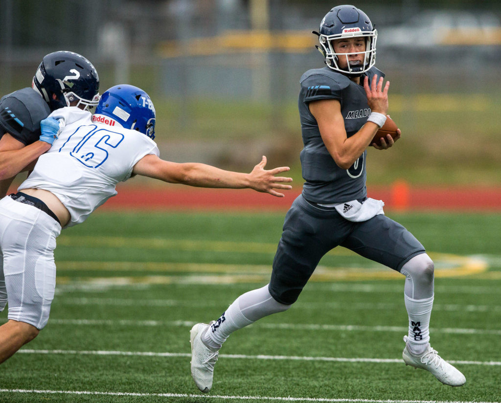 Meadowdale's Hunter Moen escapes a tackle during the game on Friday, Sept. 13, 2019 in Edmonds, Wash. (Olivia Vanni / The Herald)