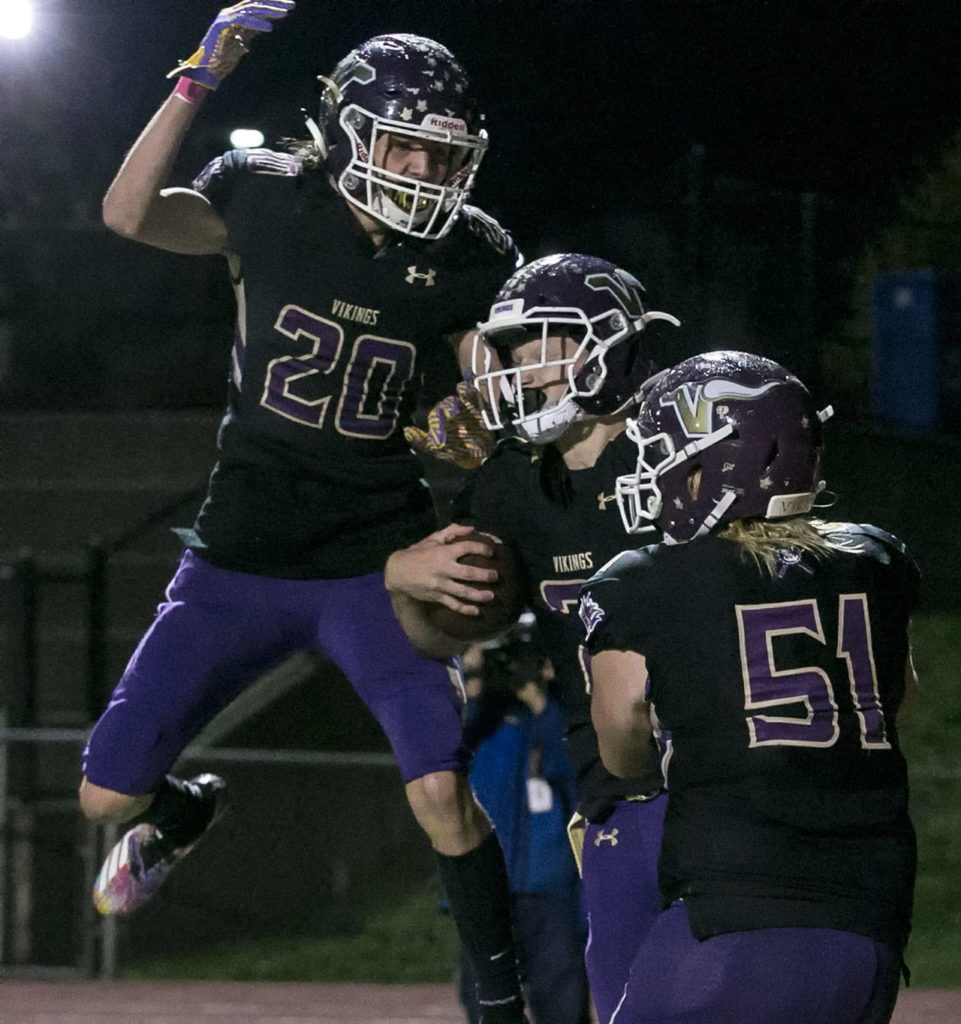 Lake Stevens' Joe Gonzales (left) celebrates with Mason Gack (right) Jackson Grafe's (center) touchdown Friday night at Lake Stevens High School on October 5, 2018. (Kevin Clark / The Herald)