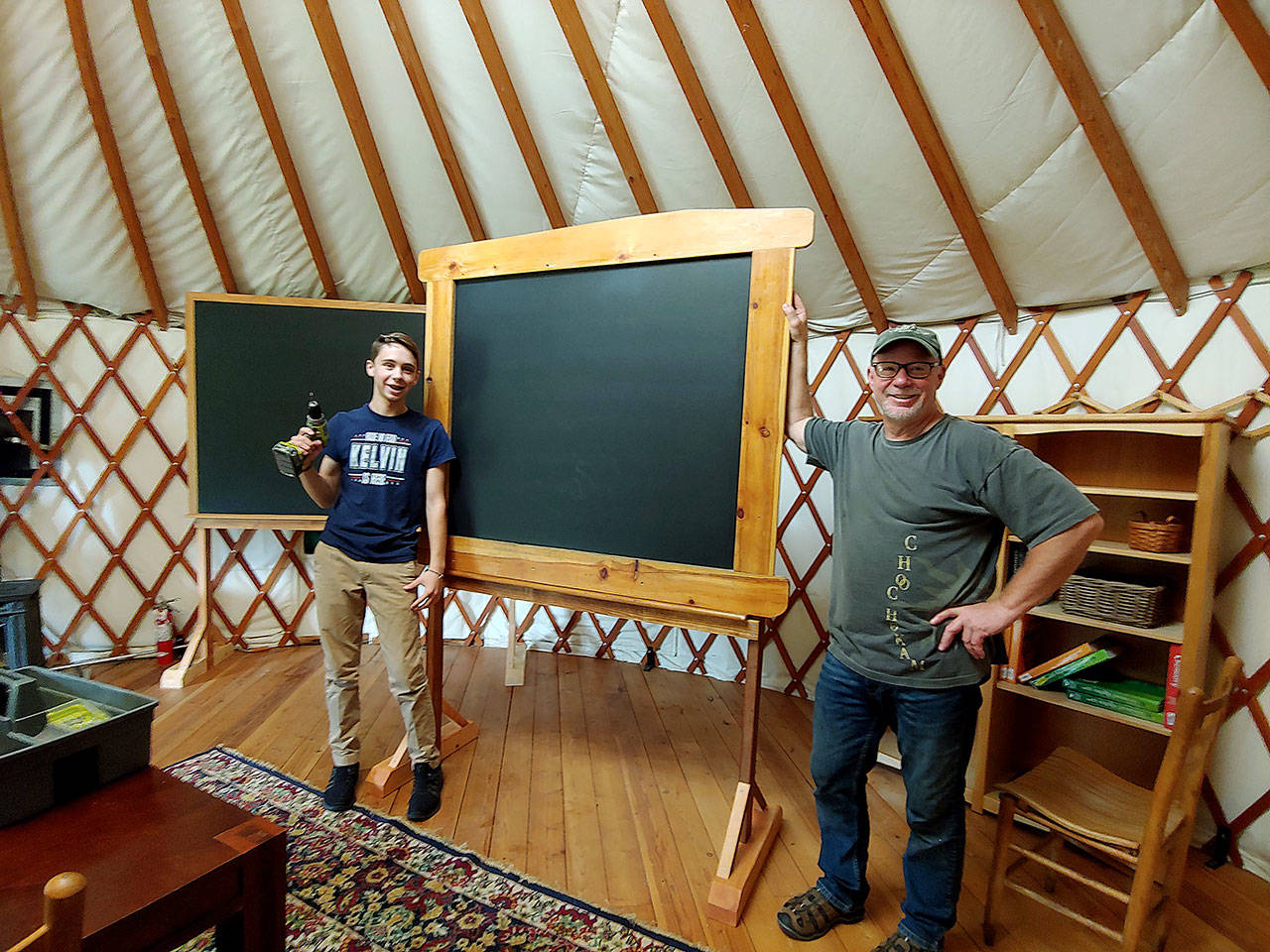 Woodhaven Faculty Liaison Kent Ratekin and freshman Kelvin Jenkins put together a chalkboard at the Organic Farm School classroom. (Marli Jenkins)