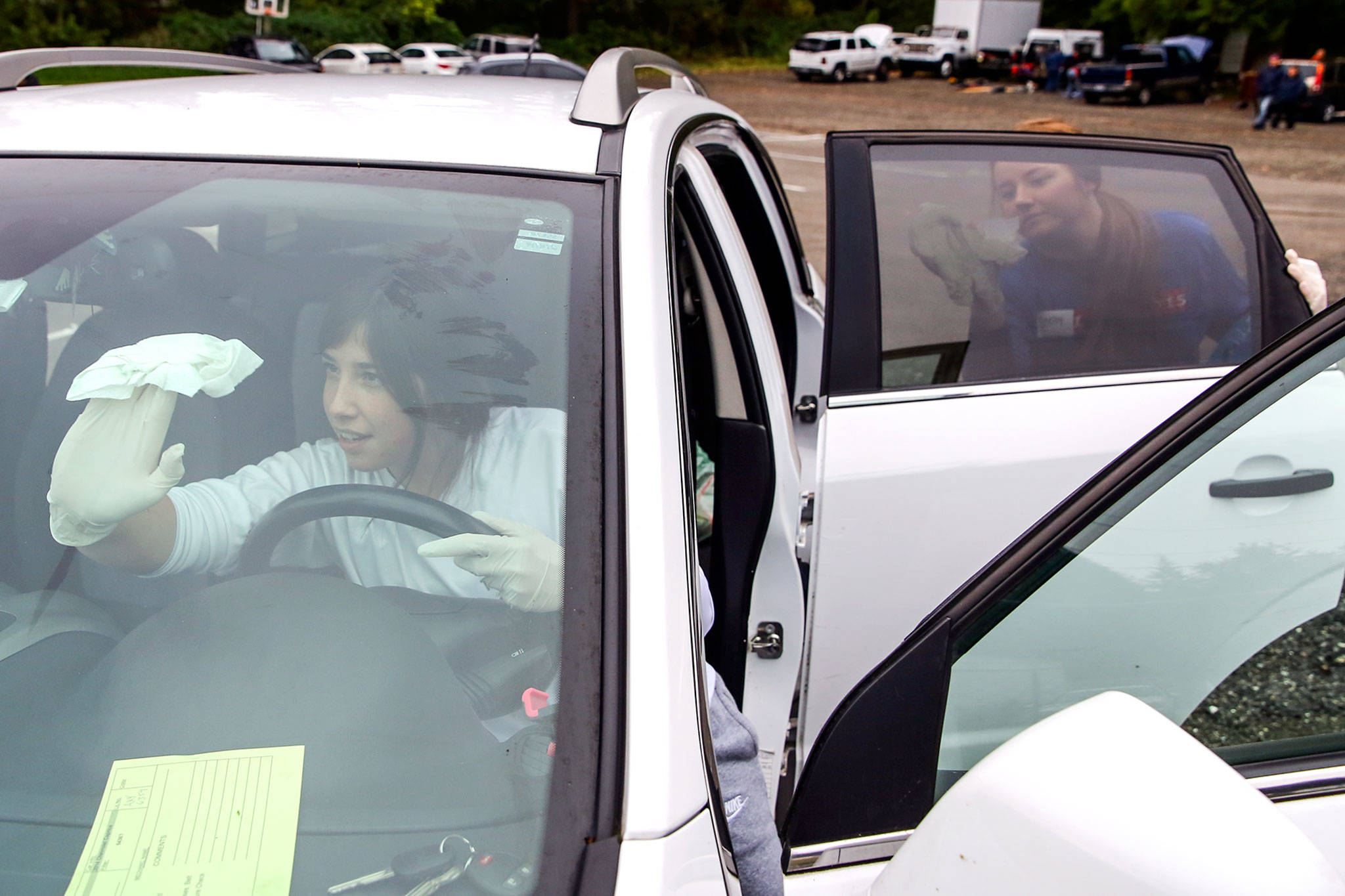Brianna Phillips (left) and Shelby Lyon detail a car at View Church in Snohomish. (Kevin Clark / The Herald)