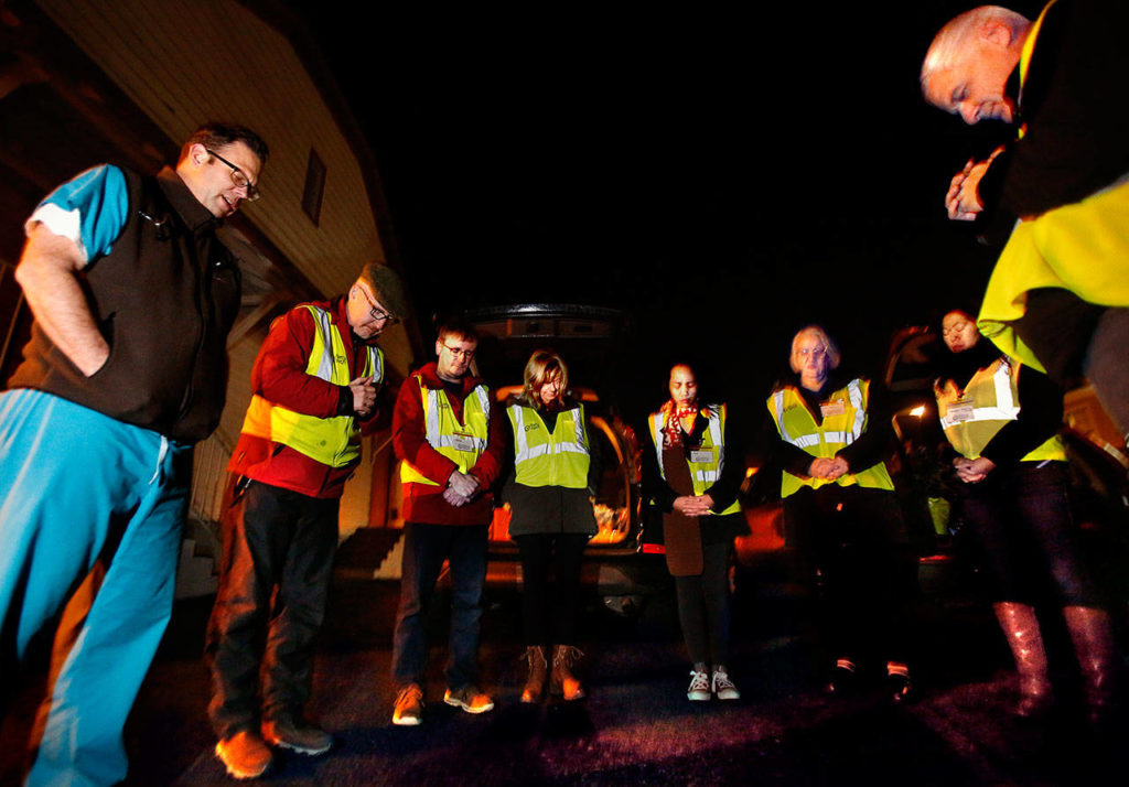 MercyWatch volunteers pray together in an Everett church parking lot before heading out to offer food, supplies and medical care to people living on the streets. From left are Dr. Jimmy Grierson, Deacon Dennis Kelly, Rodney Wagar, Sheri Dehaan, Ann Salonen, Gail Pyper, Amanda Dahl and Duane Schireman. (Dan Bates / The Herald)