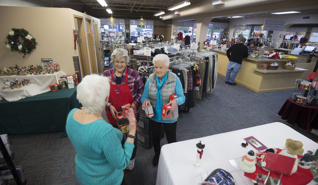Volunteer Eunice Smith, left, and Sandi Sharp, right, talk with another volunteer in the Assistance League of Everett thrift store. (Andy Bronson / The Herald)