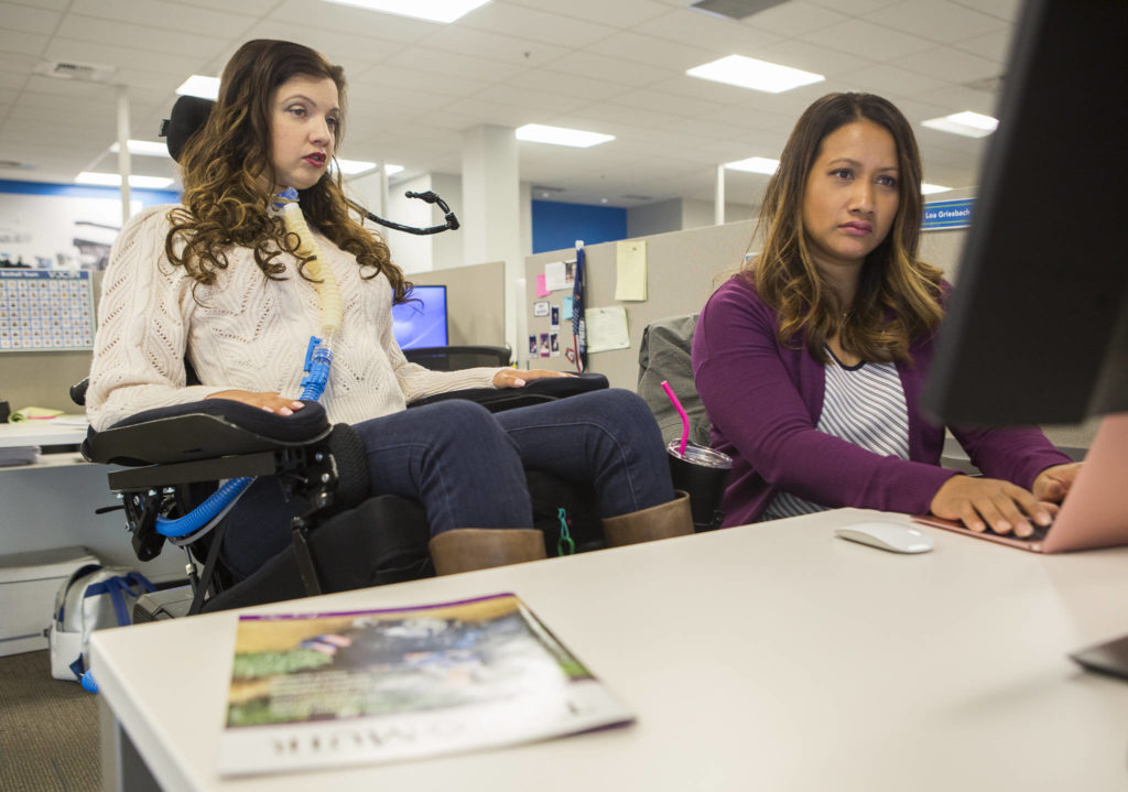Loa Griesbach (left) works on her blog with the help of nurse Sophany Elginon at her desk at Ventec Life Systems in Bothell. (Olivia Vanni / The Herald)
