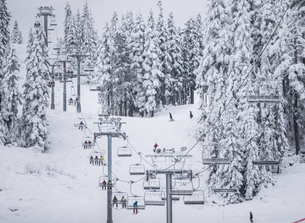 People ride the chairlifts as skiers and snowboarders make their way down the mountain on opening day at Stevens Pass on Wednesday. (Olivia Vanni / The Herald)