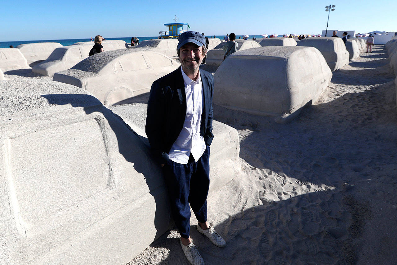 Artist Leandro Erlich, of Argentina, poses with his work featuring cars sculpted in sand stuck in a traffic jam. (AP Photo/Lynne Sladky)
