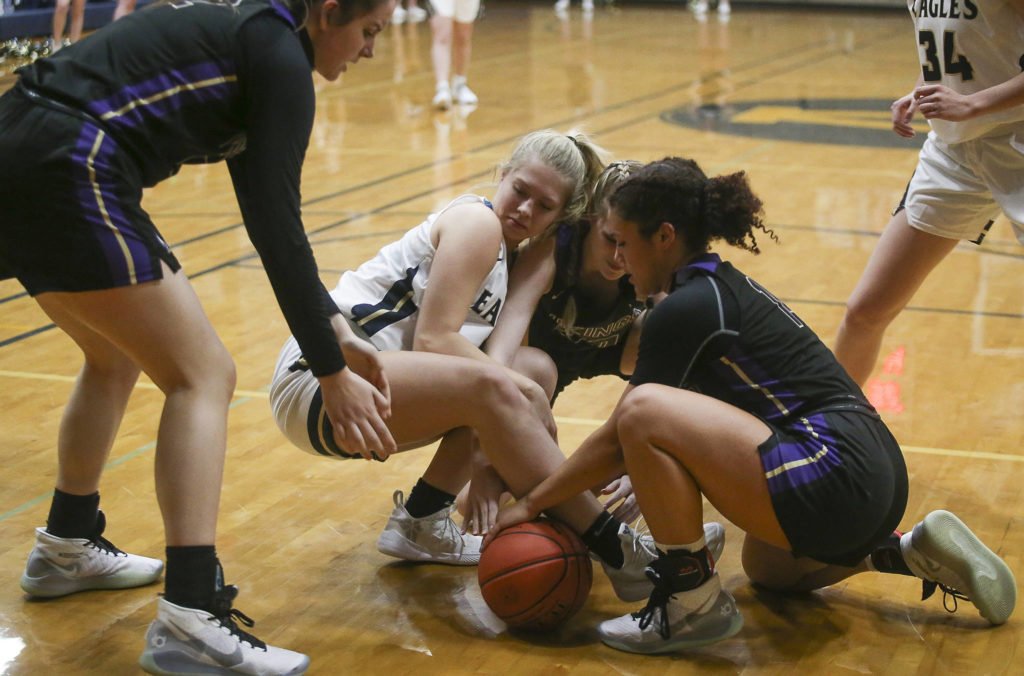 Players battled for a loose ball as the Arlington Eagles lost to the Lake Stevens Vikings 57-54 in a girls' basketball game on Friday, Dec. 6, 2019 in Arlington, Wash. (Andy Bronson / The Herald)