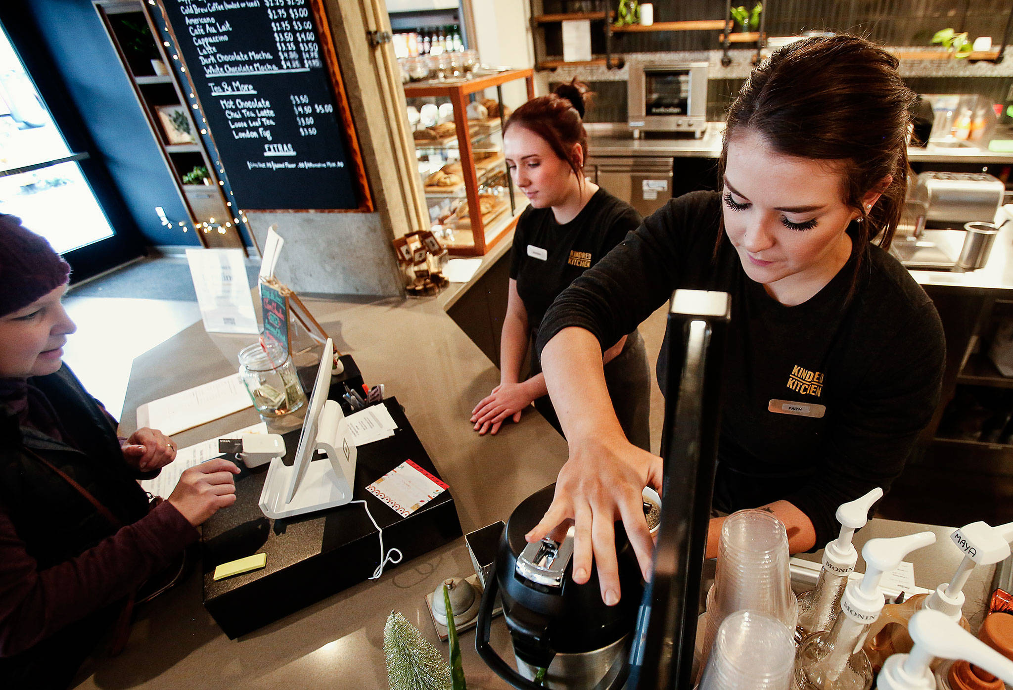 Makenna Chapman helps customers at the cash register while barista Faith Littlefield (right) prepares coffee Friday at Kindred Kitchen. (Dan Bates / The Herald)