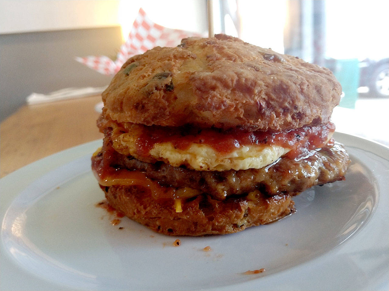 The Lumberjack sandwich at Biscuit & Bean in Lake Stevens is made with a sausage patty, egg, cheddar and tomato jam on either a buttermilk or cheddar onion biscuit. (Sara Bruestle/The Herald)