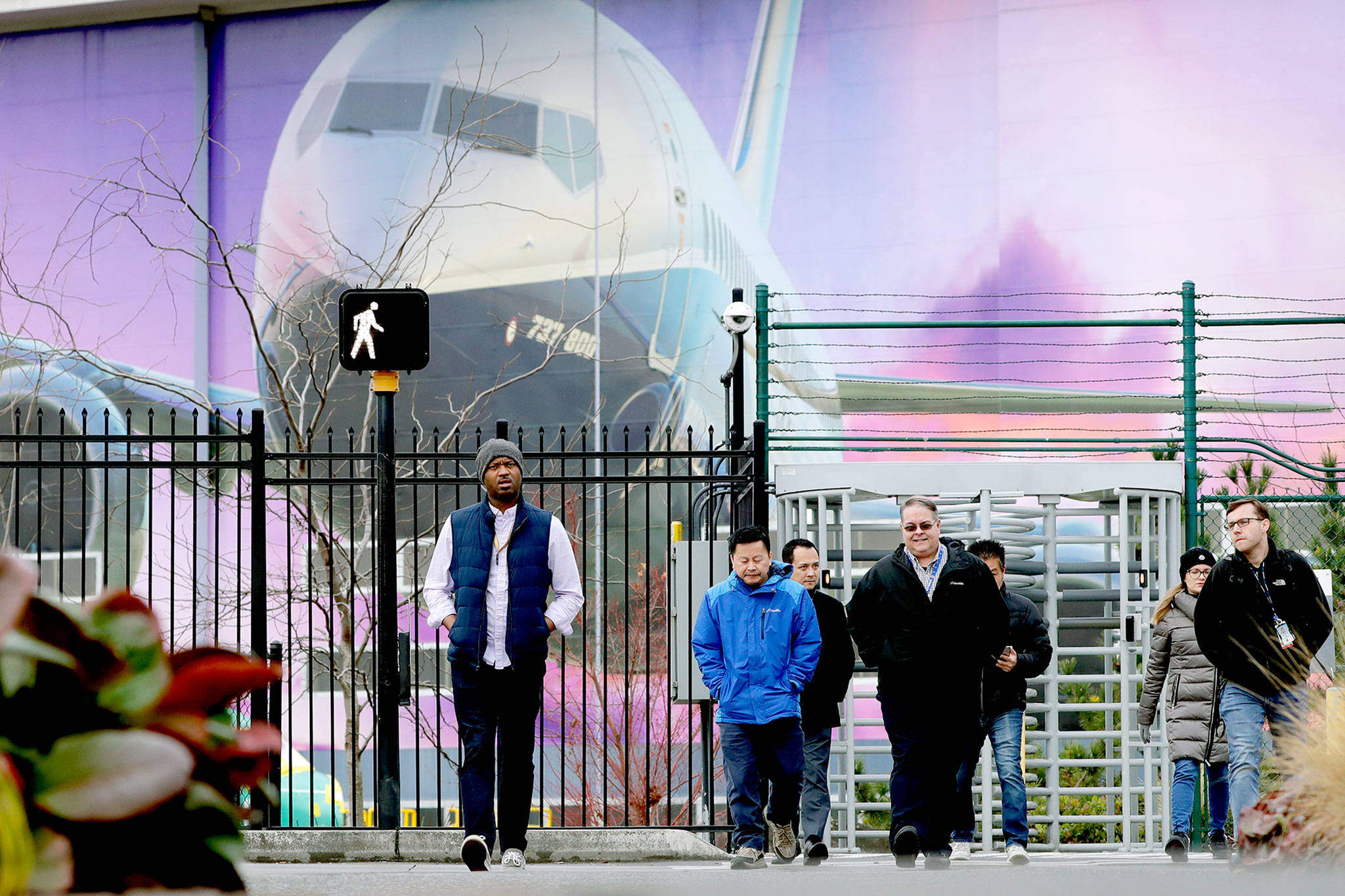 Boeing workers on Monday exit the Renton plant in front of a giant mural of a 737. (AP Photo/Elaine Thompson)