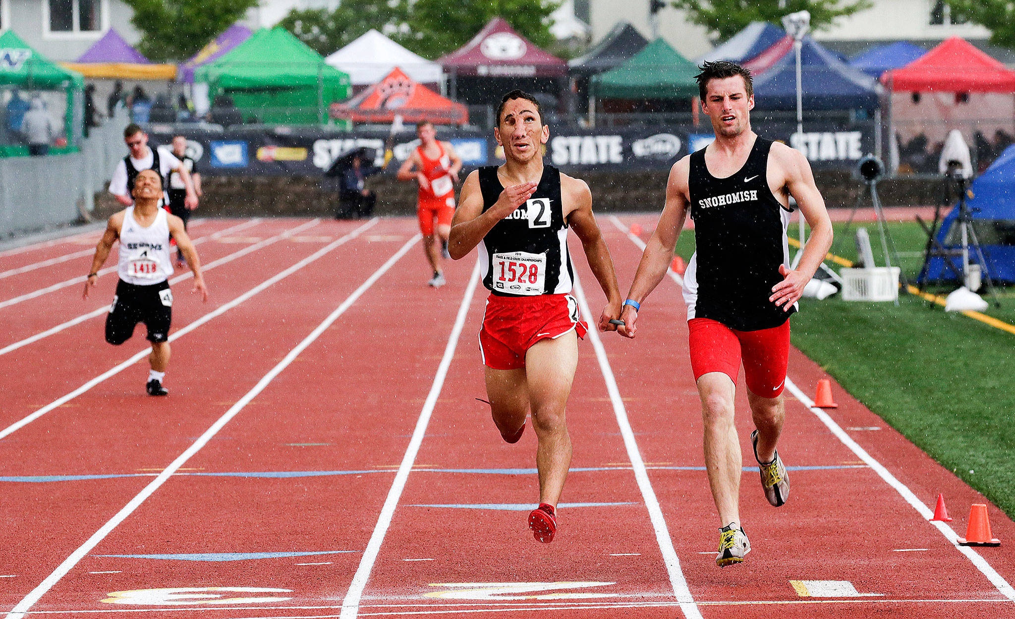 Snohomish's Humoody Smith (1528) and guide Zebedee Kumley cross the finish line first in the 200 Meter Ambulatory Dash at the Washington State track finals at Mount Tahoma Stadium on May 25, 2019, in Tacoma. (Andy Bronson / The Herald)