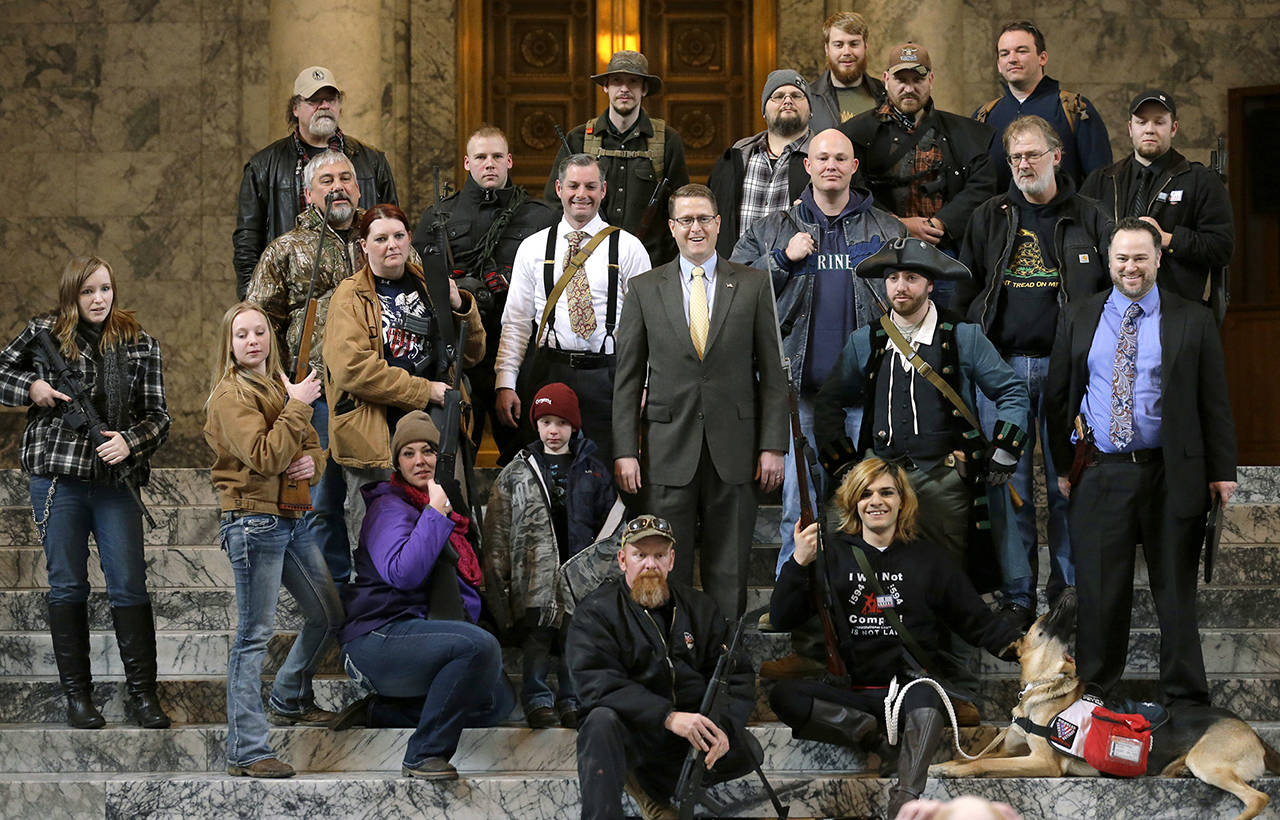 In this 2015 photo, Washington state Rep. Matt Shea, R-Spokane Valley, in suit and yellow tie at center, poses for a group photo with gun owners inside the Capitol in Olympia, following a gun-rights rally. (AP Photo/Ted S. Warren, File)